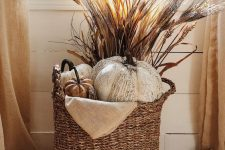 a Thanksgiving arrangement in a basket – faux pumpkins and wheat plus some burlap is great for fall, too