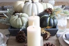 a neutral Thanksgiving centerpiece of green pumpkins, candles and pinecones is a great idea for a rustic tablescape