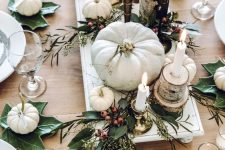a neutral Thanksgiving table with white pumpkins, leaves, berries, candles and tree stumps and slices is very cool