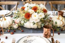 a neutral modern farmhouse Thanksgiving tablescape with a grey runner and chargers, printed plates, napkins and a pumpkin with neutral and bold blooms, copper mugs and cutlery
