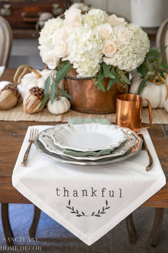 a neutral rustic Thanksgiving table with a plaid runner, a white napkin, a copper mug, a bucket with hydrangeas and roses and acorns