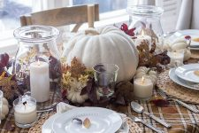 a neutral rustic Thanksgiving tablescape with a plaid runner, woven chargers, pumpkins, dark foliage and candles around