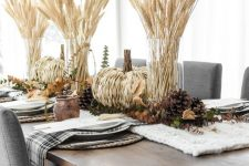 a rustic fall or Thanksgiving tablescape with a knit runner, pinecones, woven pumpkins, greenery and wheat is love