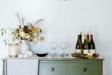 a simple Thanksgiving bar with a gold banner, pumpkins and a bold floral arrangement is a gorgeous idea
