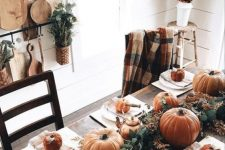 a simple rustic Thanksgiving table with a lush greenery runner, orange pumpkins and gourds, copper teapots and mugs