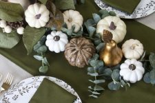 a stylish Thanksgiving tablescape with green linens, pumpkins, greenery and candles plus printed plates