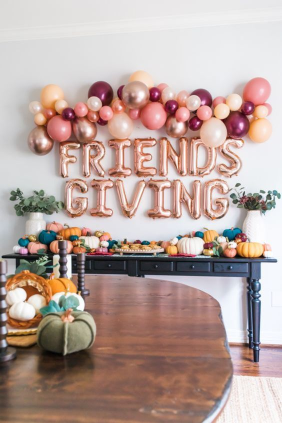 bright Thanksgiving decor with bold pumpkins of various sizes, greenery, bold ballons and balloon letters over the table