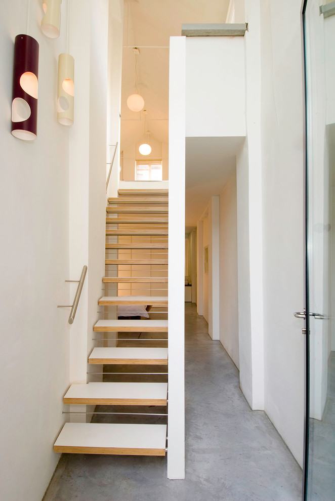 Removing stair risers can make the staircase transparent so it won't look so bulky. (Threefold Architects)