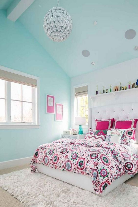 a bright and cheerful teen bedroom with an upholstered white bed, pastel mint walls and ceiling, a sphere chandelier and a shelf over the bed