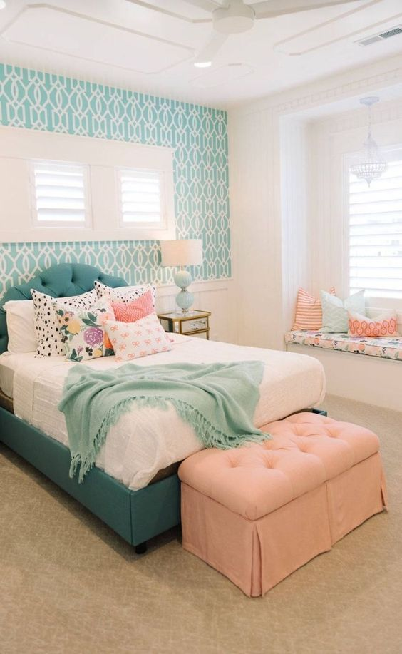 a bright teenage bedroom with a turquoise upholstered bed and a matching accent wall, a peachy ottoman and pillows