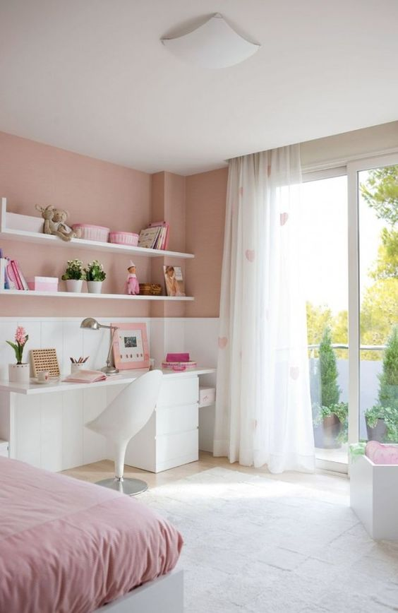 a contemporary pink teen bedroom with a white desk, heart print curtains, open shelves and a bed with pink bedding