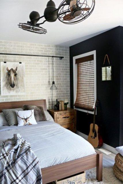 a contemporary teen bedroom with a dark and brick wall, wooden furniture, metal fans and neutral textiles