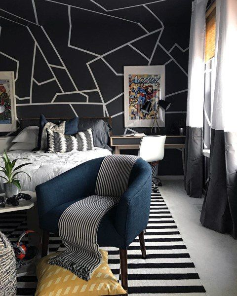 a contemporary teen bedroom with a graphic wall, a striped rug and pillow, color block curtains and a desk in the corner