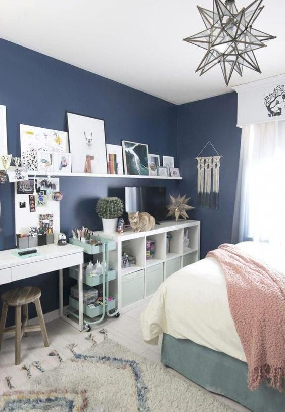 a contemporary teen bedroom with storage units from IKEA, a white desk, an open shelf, navy walls and a comfy bed