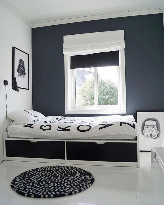 a laconic contrasting teen bedroom with black and white walls, a bed with drawers, black and white shades and artworks