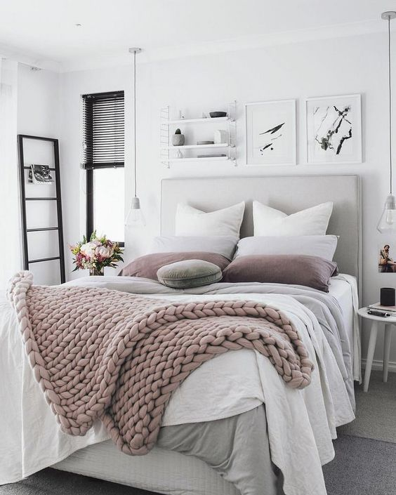 a neutral and pastel bedroom with a grey upholstered bed, layered blankets, black touches and bulbs hanging down