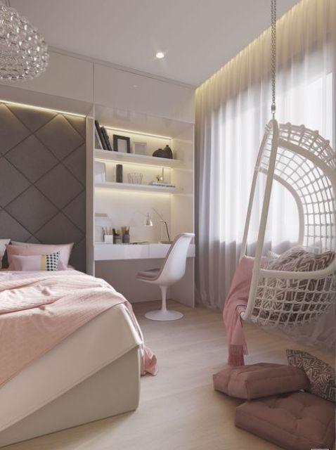 a pastel teen bedroom with a built-in bed, a built-in desk space and a hanging woven chair in the corner