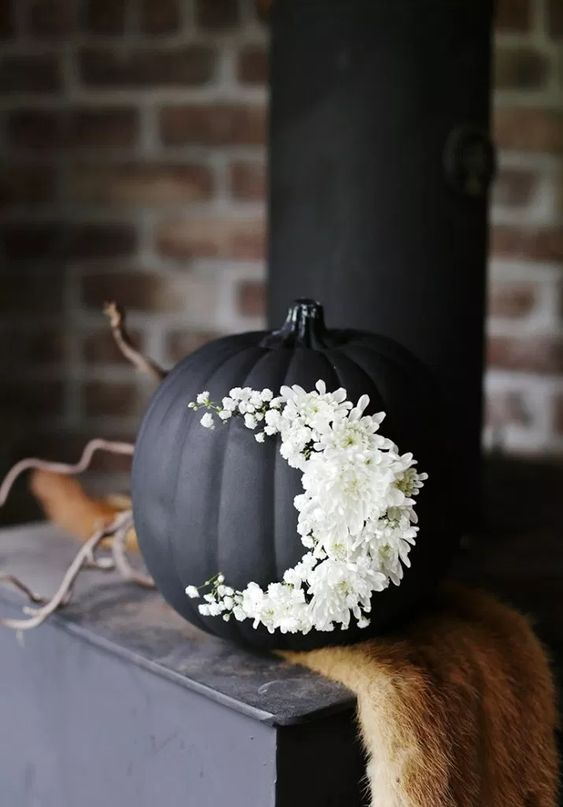 a matte black pumpkin decorated with white flowers is a very chic and beautiful Halloween decor idea