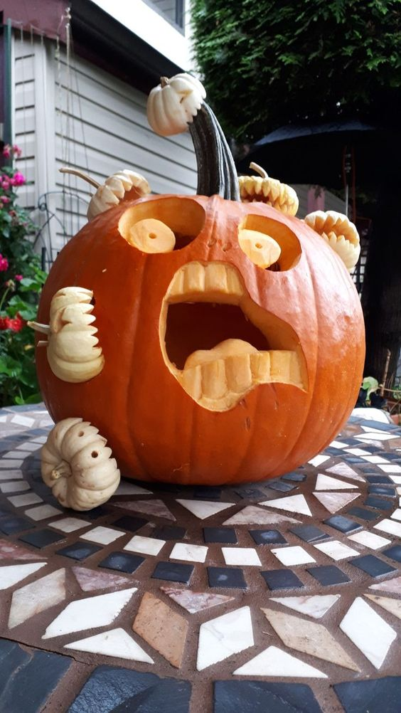 a scary carved pumpkin being eaten by other mini pumpkins is a very fun and spooky idea to realize for Halloween