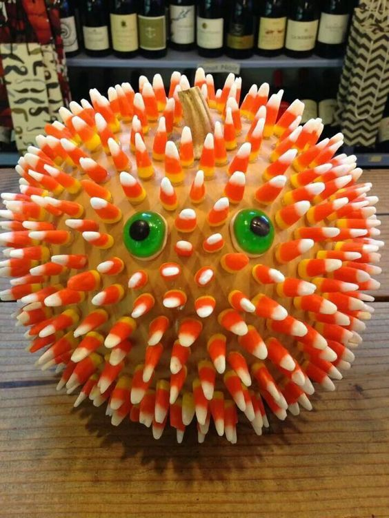 a super creative pumpkin covered with candy corns and with green eyes shows a little monster and looks very fun