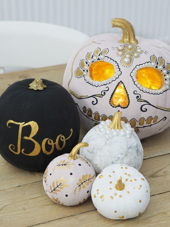 an arrangement of beautiful pumpkins - a matte black one, patterns ones and a gorgeous sugar skull styled pumpkin to finish off