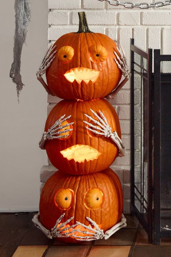 cool Halloween pumpkins stacked, with scary faces, eyes and skeleton hands are fun and cool for Halloween decor