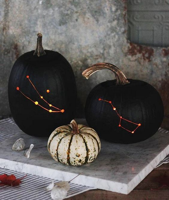 matte black constellation pumpkins are adorable for Halloween and look veyr stylish and bold, they arne't scary at all and you may use them just in the fall, too