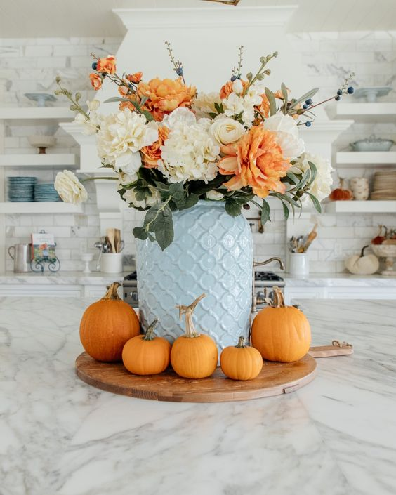 a bold modern Thanksgiving centerpiece of a blue jar, white and orange blooms and orange pumpkins around for Thanksgving