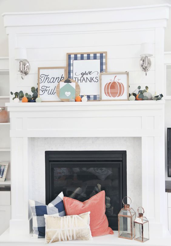 a bright Thanksgiving mantel with bold signs, greenery and mini pumpkins and matching pillows at the fireplace