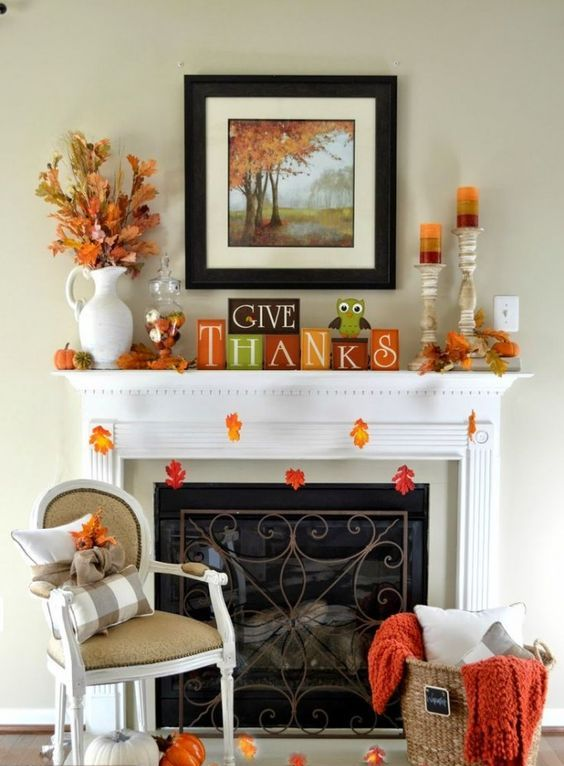 a bright Thanksgiving mantel with colorful leaves, colorful striped candles, bright cubes, dried leaf arrangements and blankets and pillows