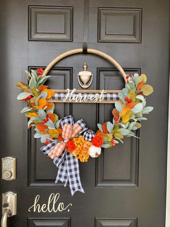 a bright Thanksgiving wreath of a hoop with faux leaves, berries, plaid ribbon and some mini colorful gourds is amazing