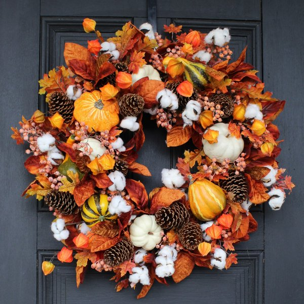 a bright Thanksgiving wreath with pinecones, gourds, pumpkins, leaves and dried blooms is a very eye-catchy solution