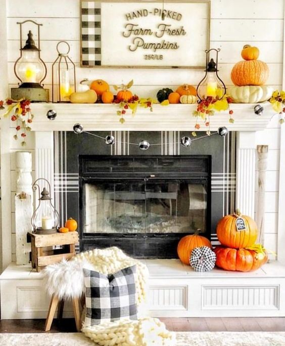 a bright and fun Thanksgiving mantel with bold pumpkins, bright leaves, candle lanterns and a plaid ball garland