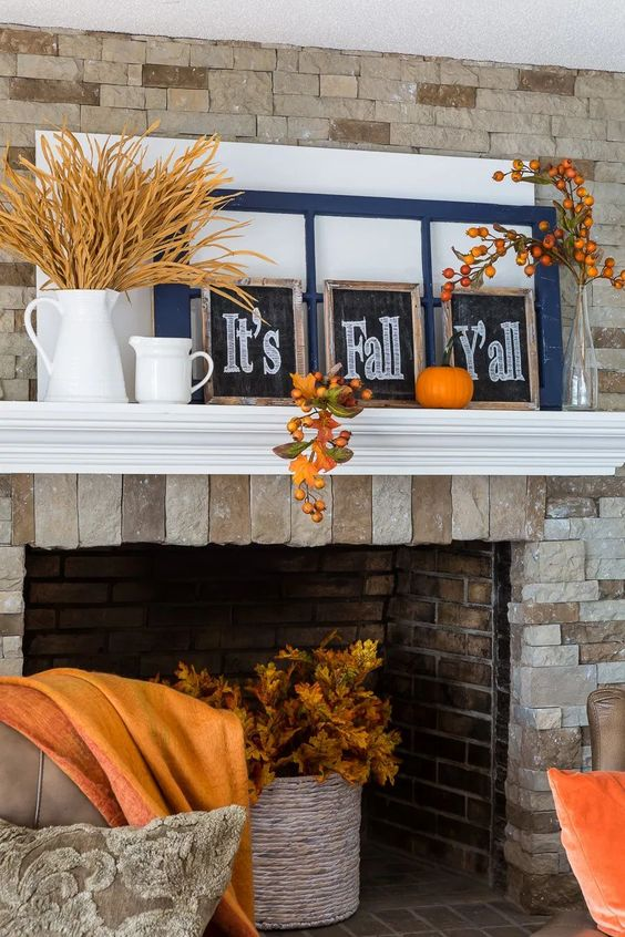 a bright and simple Thanksgiving mantel with wheat in a jug, chalkboard signs, window frames, bold pumpkins and fruits