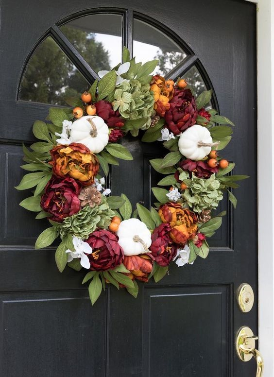 a bright fall or Thanksgiving wreath of leaves, white gourds and bold faux blooms is a stylish and timeless decoration