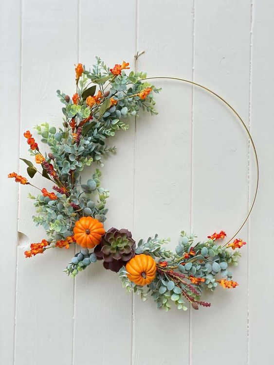 a bright fall or Thanksgiving wreath partly decorated with faux greenery, bold orange blooms, mini gourds and a succulent is chic