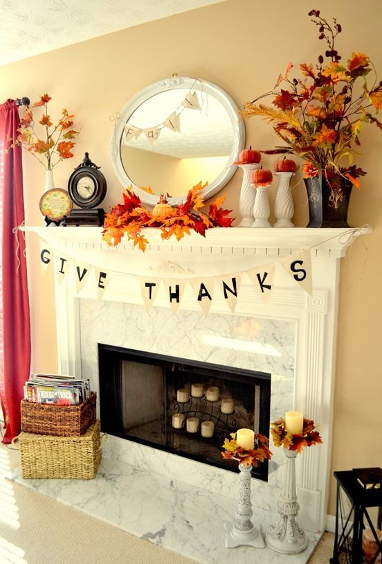a bright rustic Thanksgiving mantel with bold leaf arrangements, pumpkins on stands, some banners and candles in candleholders