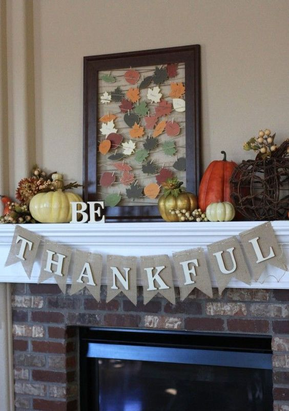 a bright vintage Thanksgiving mantel with bold pumpkins, berries, and string art with colorful paper leaves
