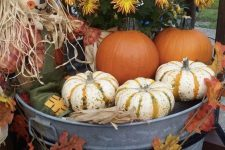 a bucket with bold blooms, leaves, pumpkins and a scarecrow is a pretty outdoor decoration for Thanksgiving