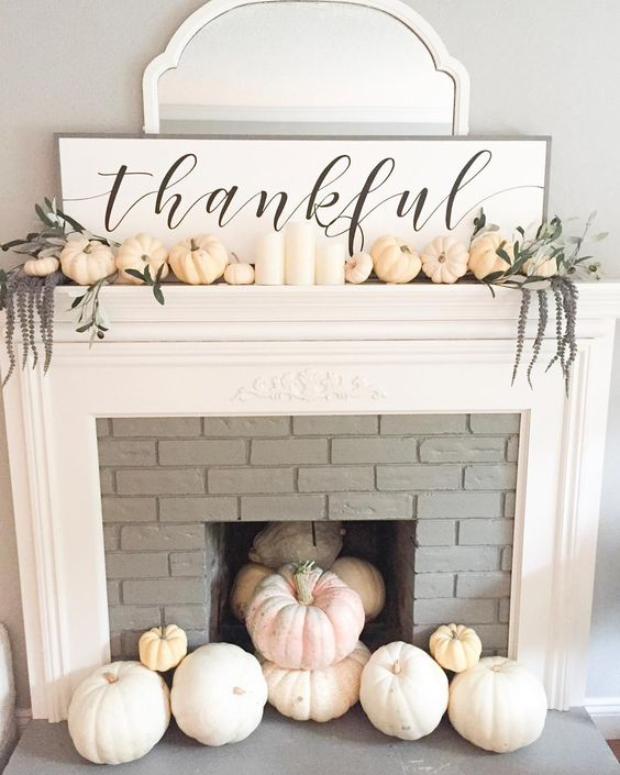 a chic white Thanksgiving mantel with pumpkins, long flowers, white candles, a sign and a mirror behind it