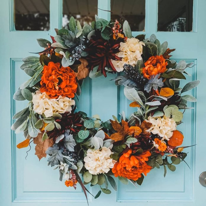 a colorful fall or Thanksgiving wreath with orange, burgundy and white blooms, greenery and foliage is amazing