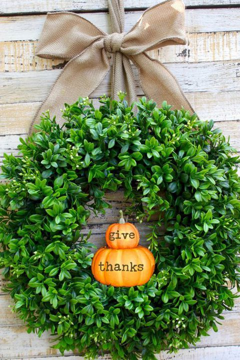 a cool and fresh Thanksgiving wreath of boxwood and little pumpkins and a large burlap bow for your front door