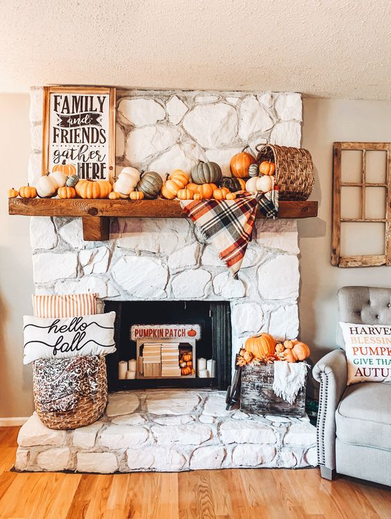 a cozy and chic Thanksgiving mantel with lots of pumpkins, a basket, a plaid blanket, a sign and some pumpkins in a crate