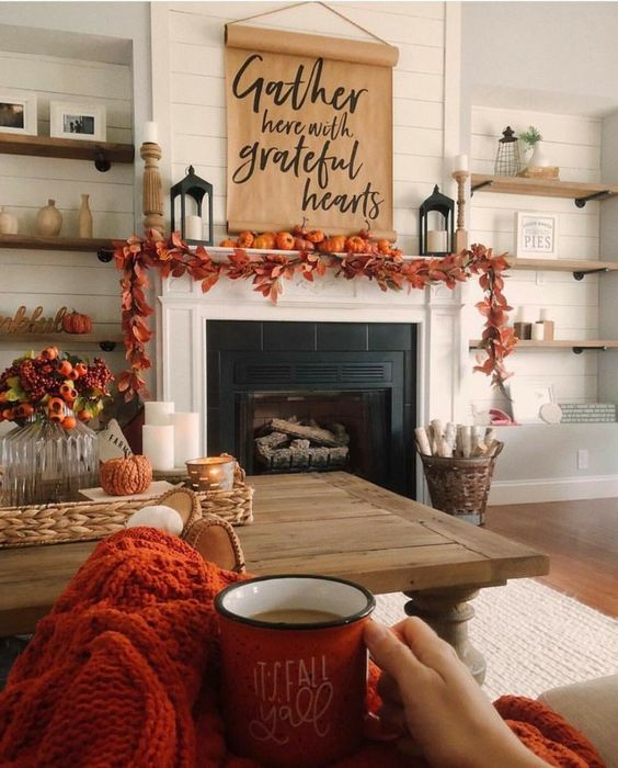 a cozy rustic Thanksgiving mantel with a bold leaf garland, orange pumpkins, a paper hanging and candle lanterns