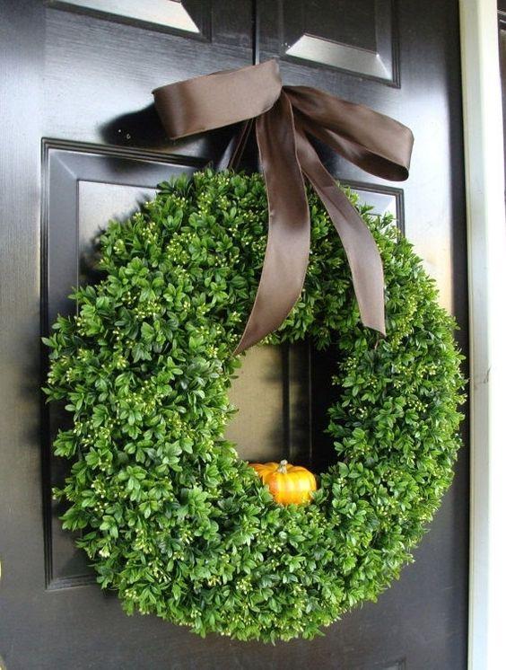 a cute fall or Thanksgiving wreath of fake greenery, a little faux pumpkin and a brown silk ribbon bow