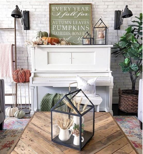a fall or Thanksgiving mantel with heirloom pumpkins, paper leaves and blooms, lanterns with wheat and some signs