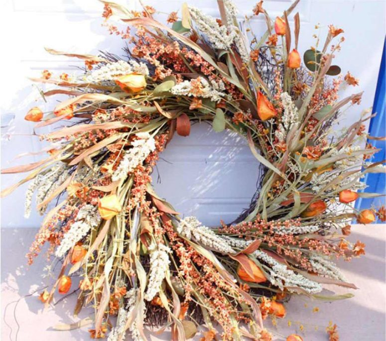 a fantastic harvest Thanksgiving wreath of herbs, leaves, greenery, dried blooms and wheat looks very natural and organic