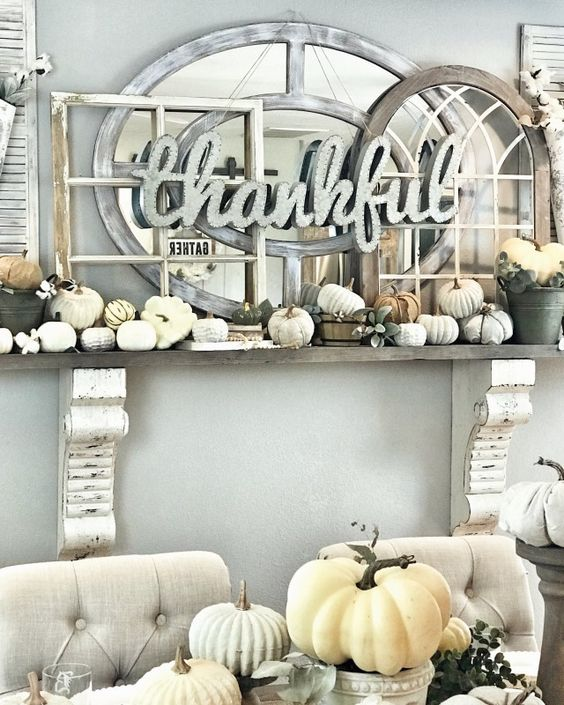 a faux Thanksgiving mantel with small neutral pumpkins, lots of window frames and a mirror plus a sign of metal