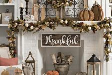 a gorgeous vintage Thanksgiving mantel with a lush dried leaf, pumpkin and wheat garland and wreath, wooden pumpkins and candles