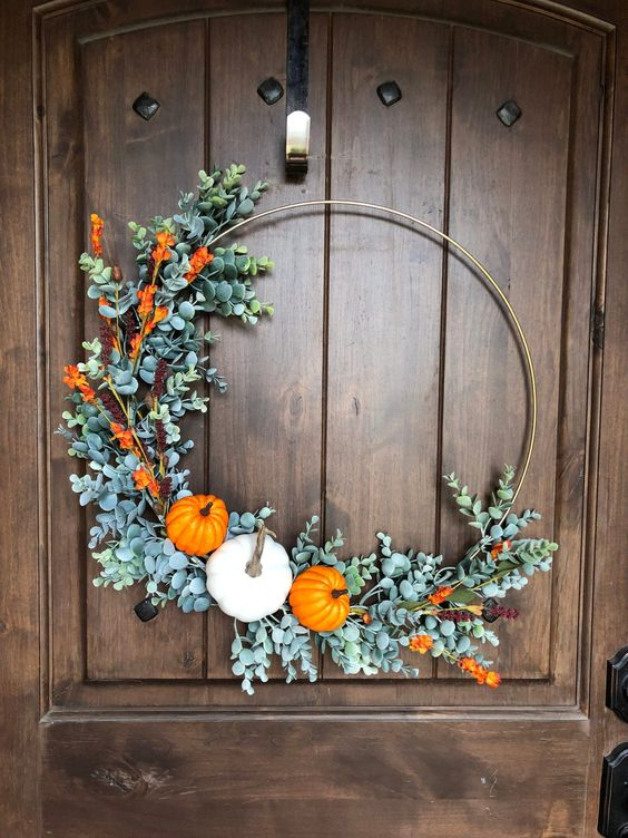 a large and bold fall or Thanksgiving wreath with faux greenery, blooms and a trio of bold pumpkins is a lovely idea